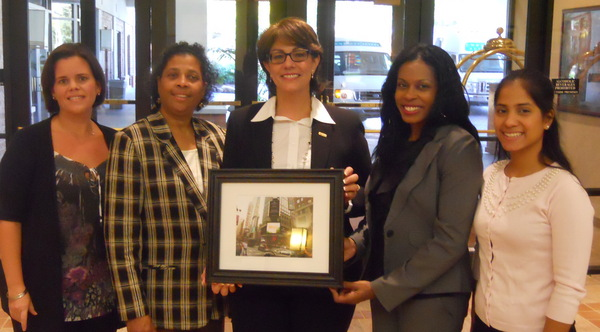NHCC receives gift from PR Newswire - framed image of their logo on Reuters Times Square Billboard. From left to right: Maggie Hernandez, PR Newswire, and NHCC staff - Betty Garcia, Pat Martinez, Zuleika Cuevas, and Claudia Torres
